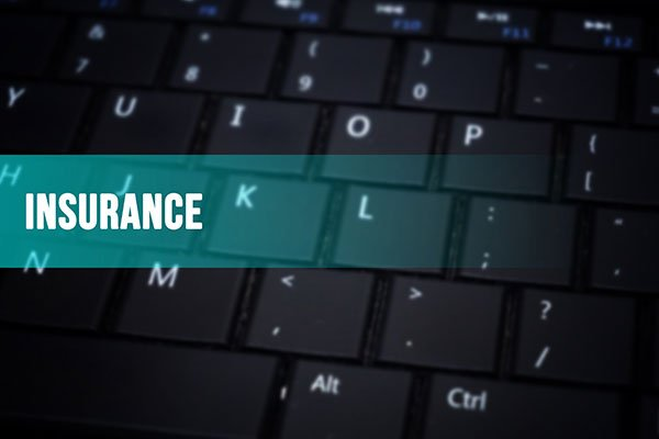 Insurance word with blurred keyboard background