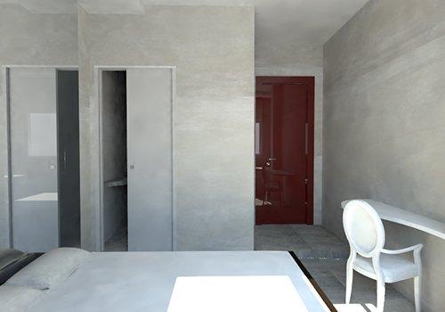 una stanza con un letto,la porta di un bagno e una sedia bianca