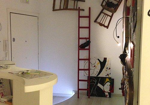 un banco ,una scala rossa appoggiata al muro e altri oggetti