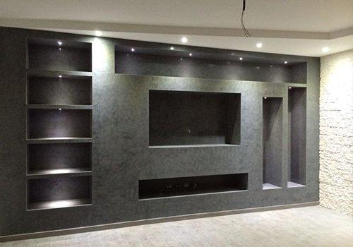 un armadio a muro color grigio con alloggio tv e altri scompartimenti