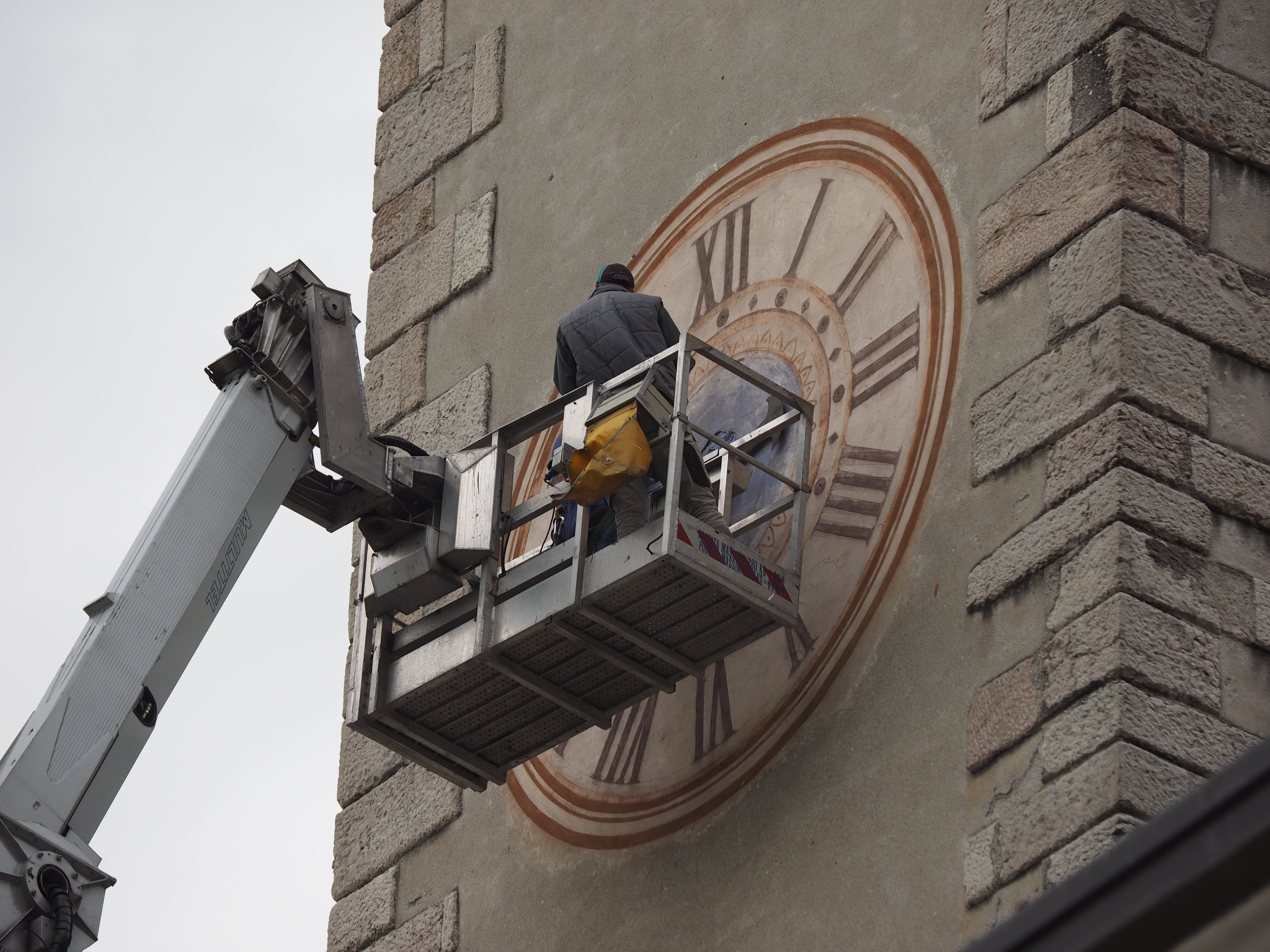 persona che ripara un orologio in una torre