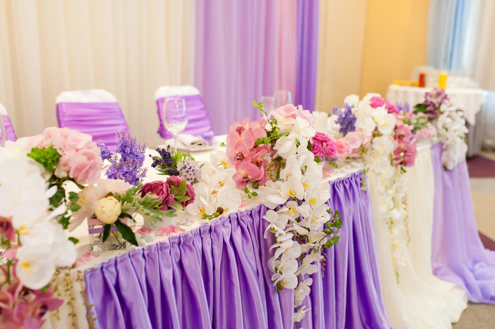 Tavola allestita con fiori bianchi e viola