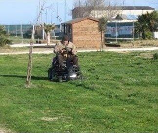 uomo alla guida di un taglia-erba