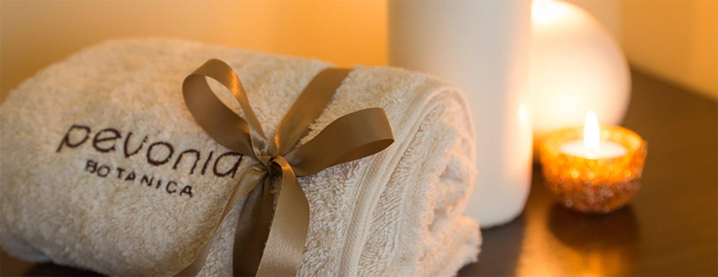 un asciugamano bianco arrotolato con scritto Pevonia Botanica e accanto delle candele accese