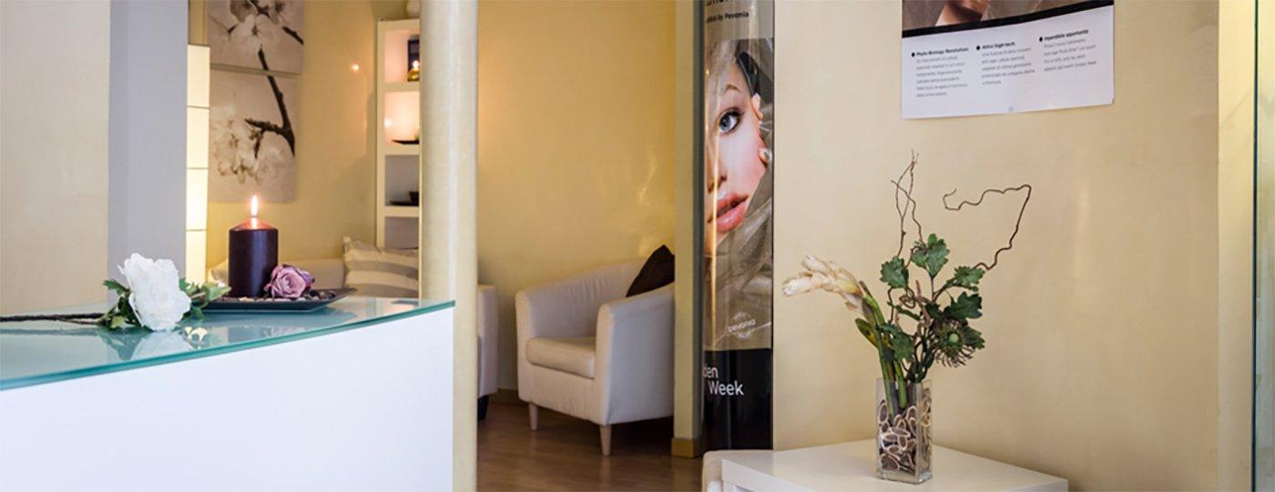 interno del centro estetico con un bancone di vetro, un monitor dietro delle mensole in vetro e sulla destra una saletta d'attesa con due sedie in pelle color panna