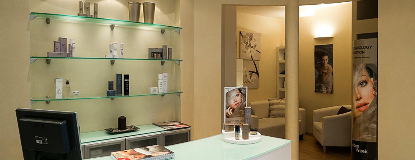 interno del centro estetico con sulla sinistra un bancone di vetro, sulla destra un tavolino con un vaso di fiori e dietro delle sedie in pelle color panna