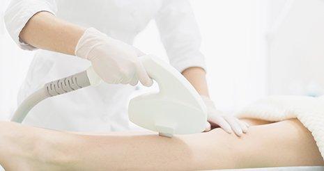 un'estetista con camice bianco e guanti mentre usa un dispositivo di epilazione sulle gambe di una donna