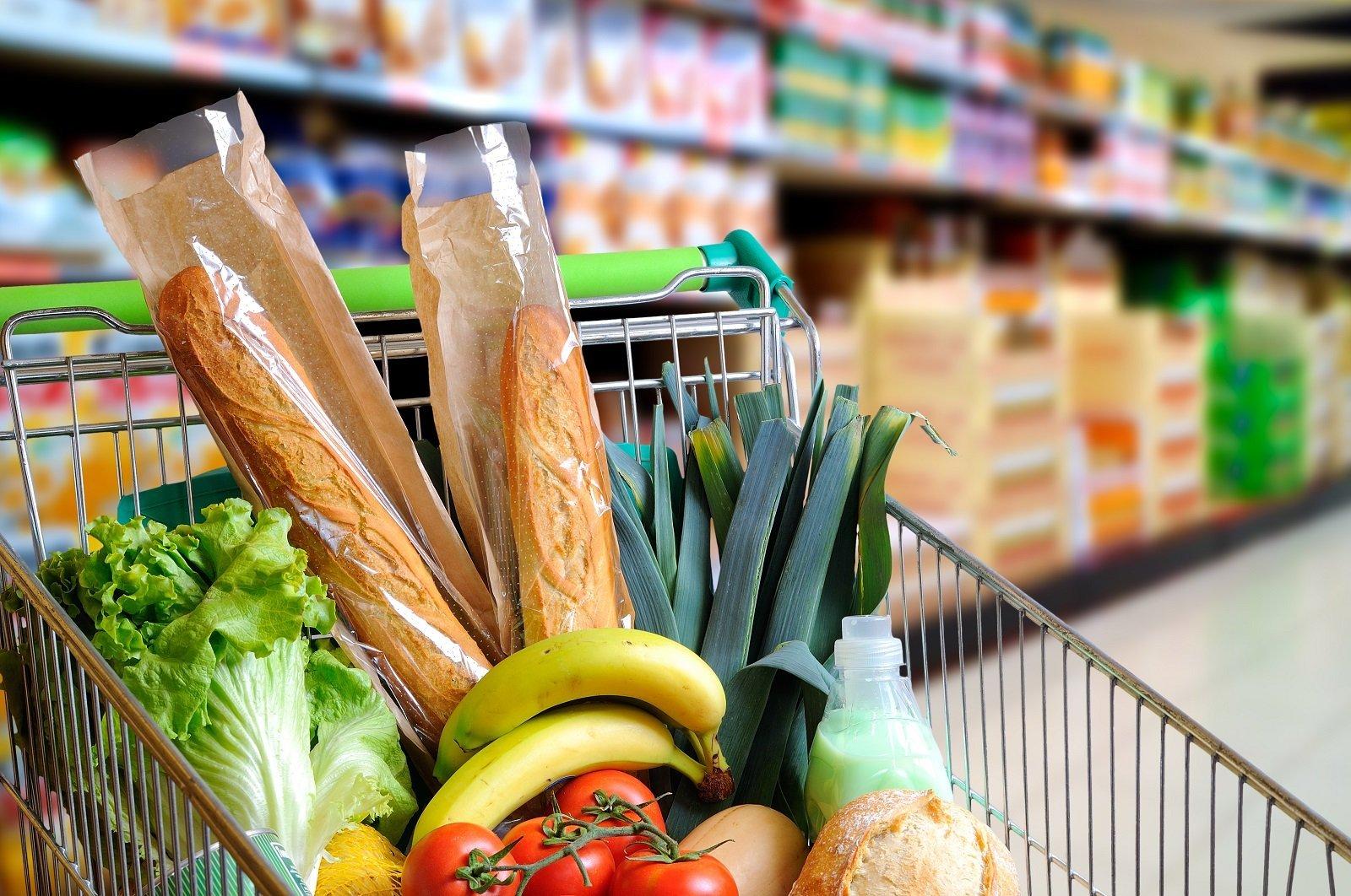 Carrello pieno di cibo nella navata del supermercato