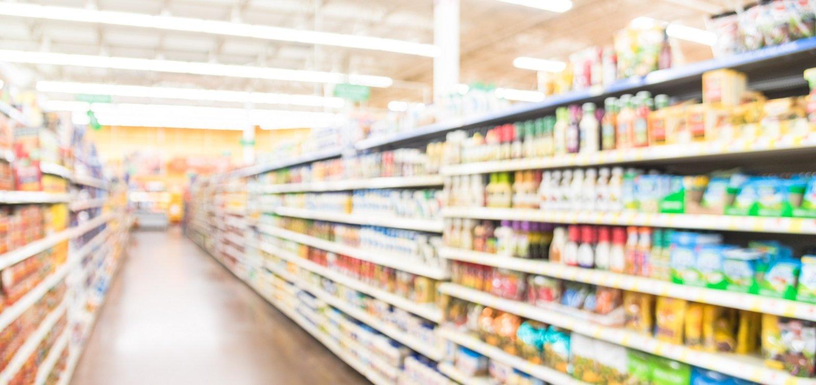 Selezione sfuocata di pasta, ketchup, condimento, salsa di pomodoro e verdura in scatola sugli scaffali in magazzino