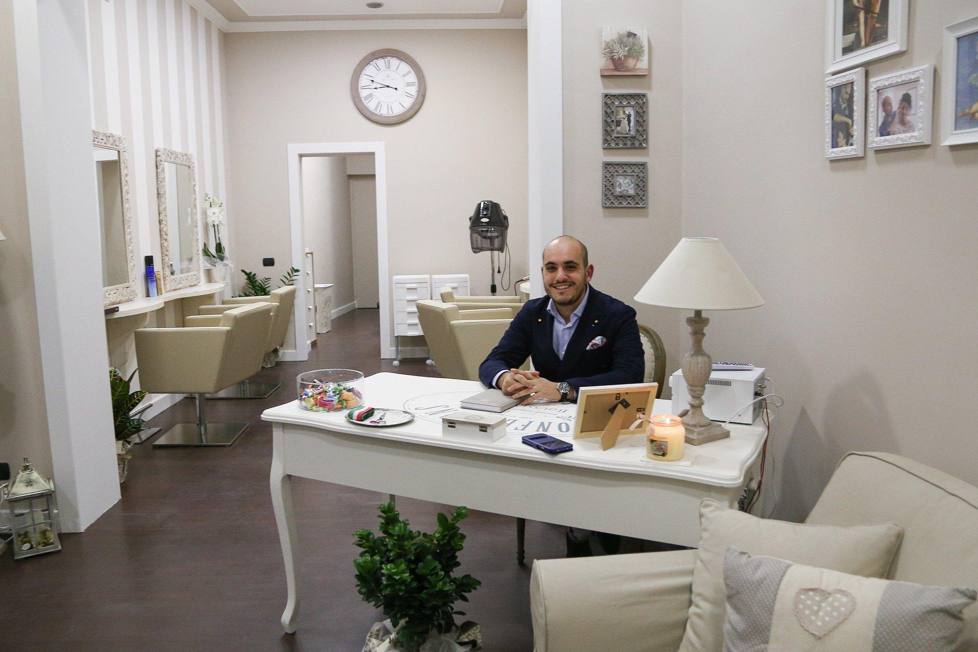 il proprietario del salone seduto alla sua scrivania