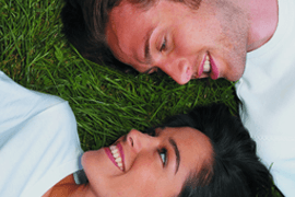 A smiling couple lying on grass