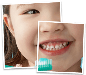 A smiling little girl with white teeth, holding a toothbrush covered with aqua toothpaste