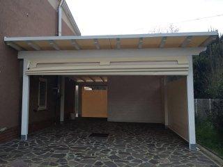 Struttura in legno chiusa con tende a pacchetto motorizzate, chiusure laterali e teli in PVC a dividere ulteriori ambienti interni