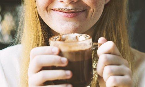 una donna mentre beve una tazza di cioccolata caldo