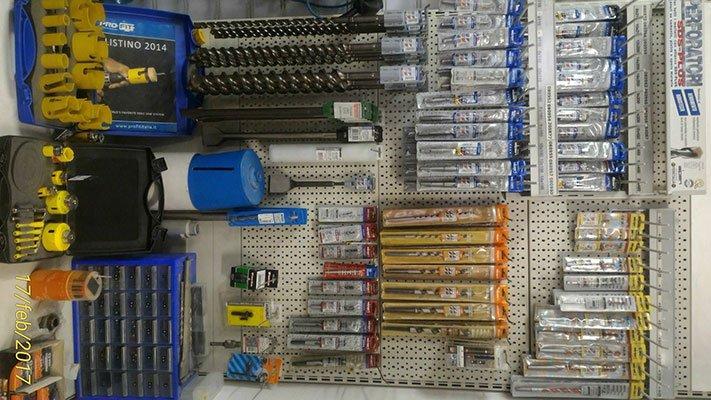 delle punte per trapani e altro materiale appese su un pannello dentro ad un negozio