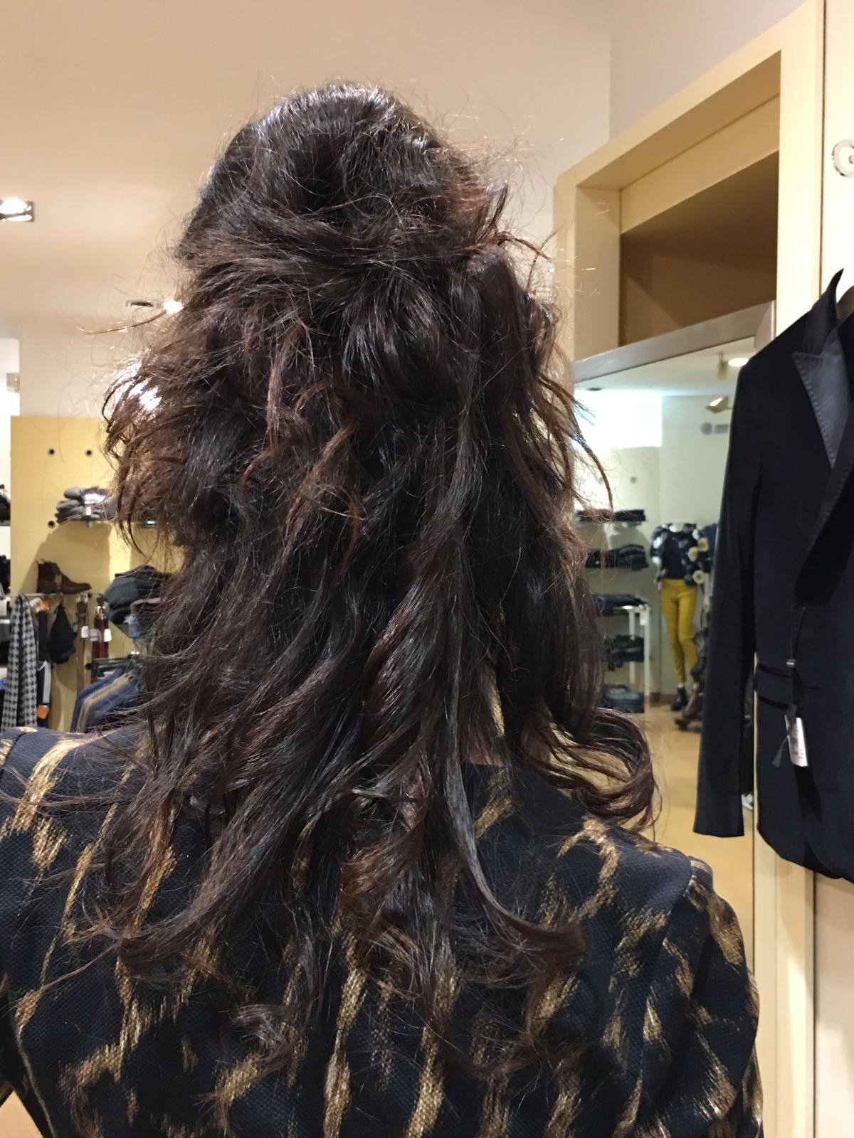 Ragazza con lunghi capelli mossi parzialmente raccolti