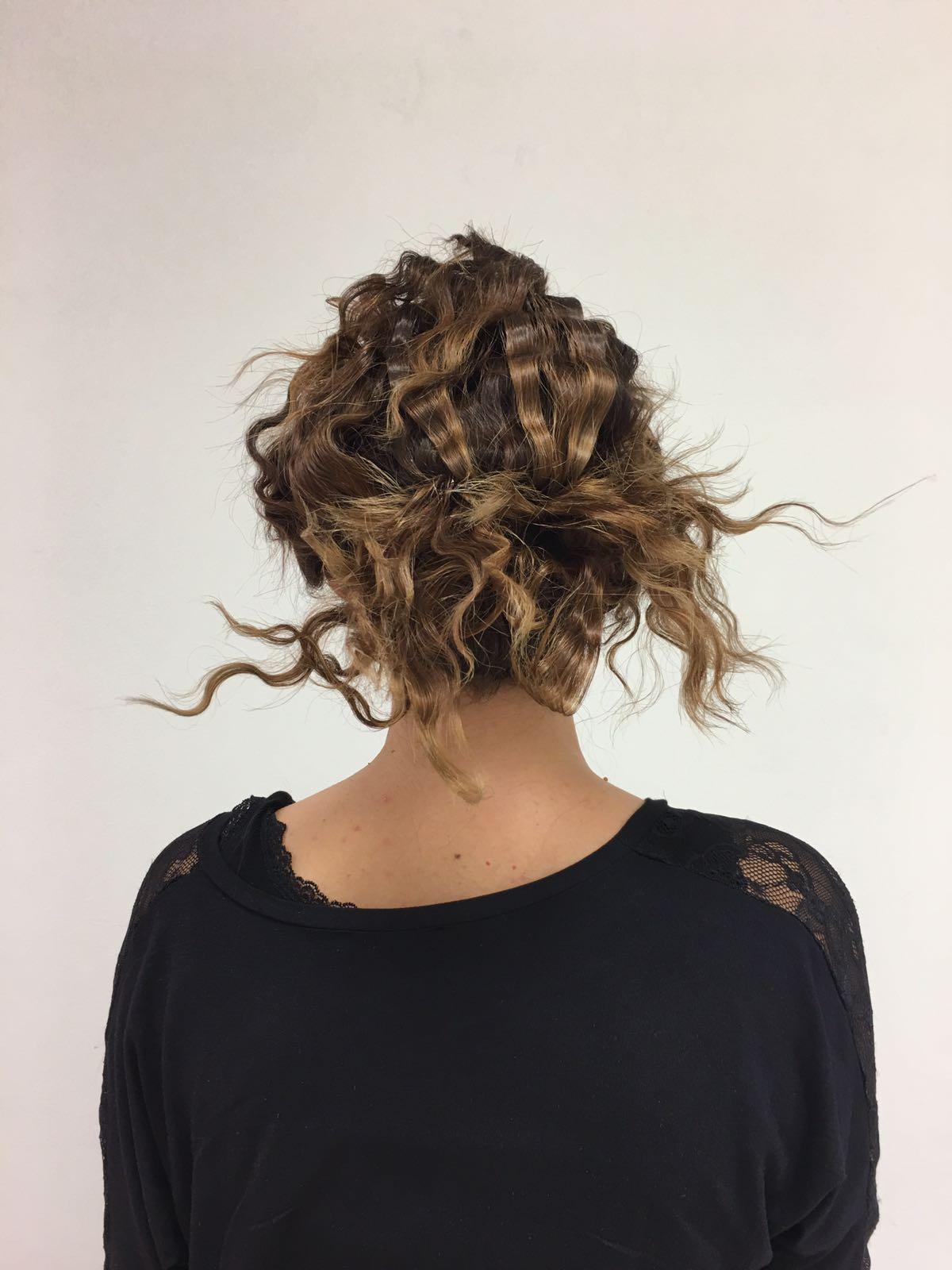 Donna con capelli frisé raccolti sulla nuca