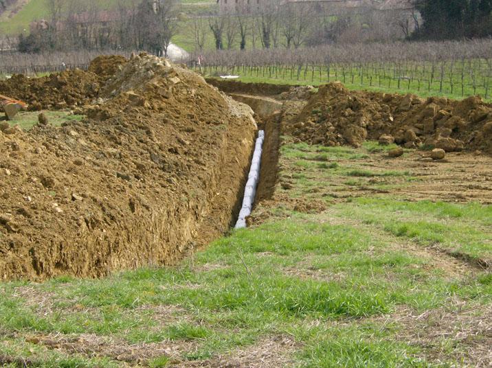 un terreno scavato e vista di una rete metallica ricoperta da un telo bianco