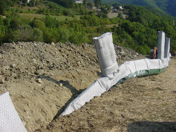 un terreno scavato con una rete metallica ricoperta da un telo bianco