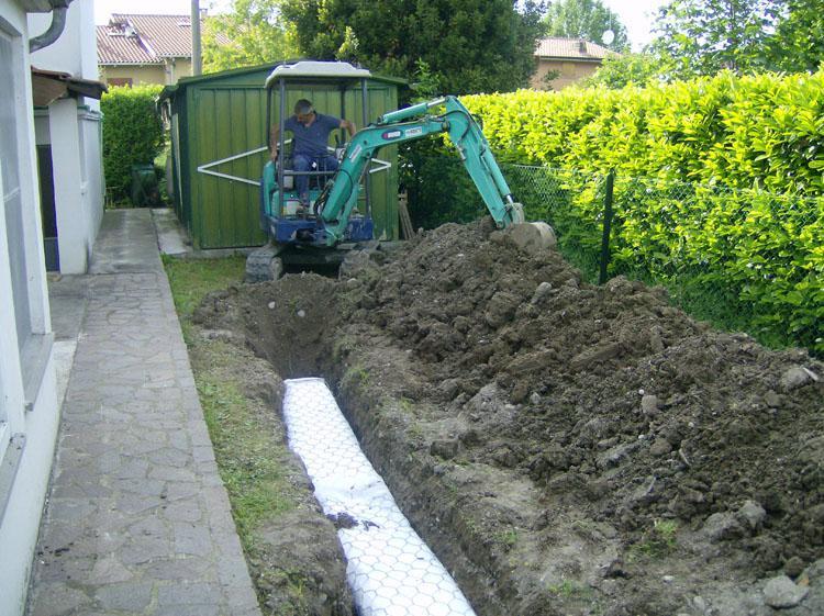 una rete metallica ricoperta da un telo bianco in un terreno scavato
