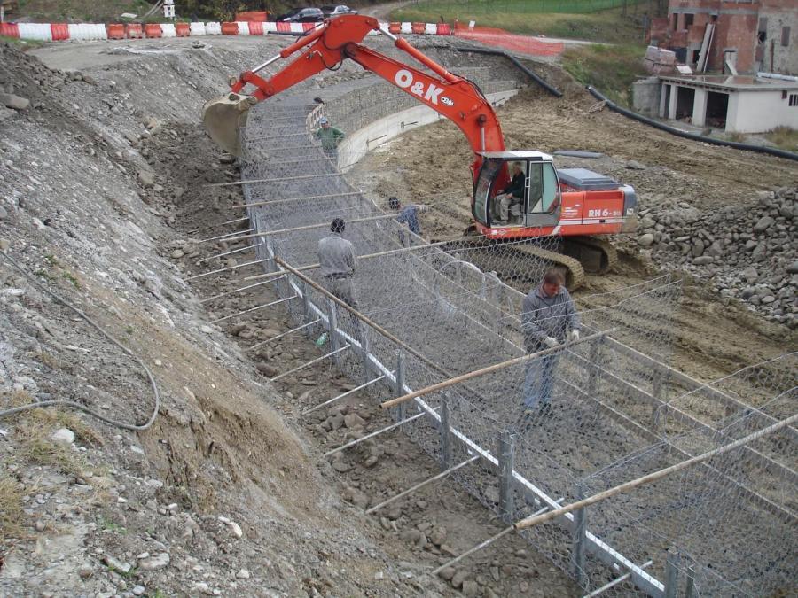 una scavatrice e degli operai vicino a una rete metallica