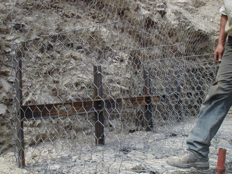 una rete metallica e la gamba di un operaio
