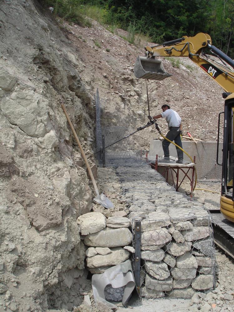 una scavatrice e un operaio al lavoro su una rete metallica