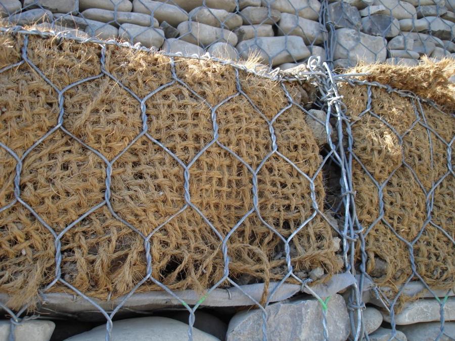 vista di una rete metallica, dei sassi e una rete di corda