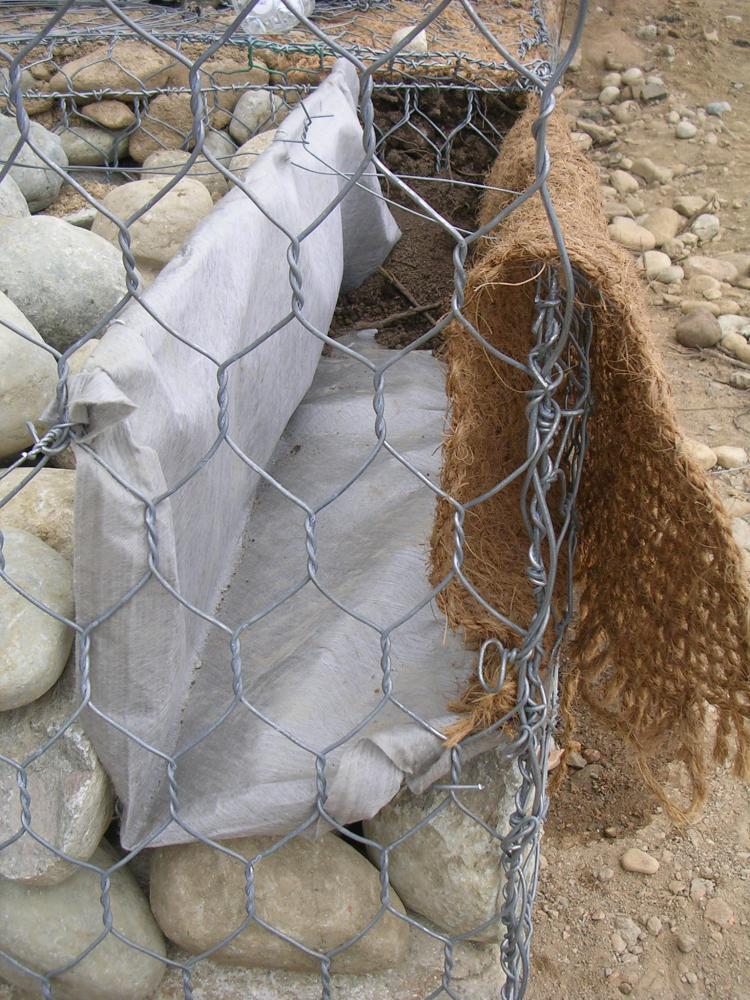 una rete metallica, dei sassi,un velo bianco e una reti di corda