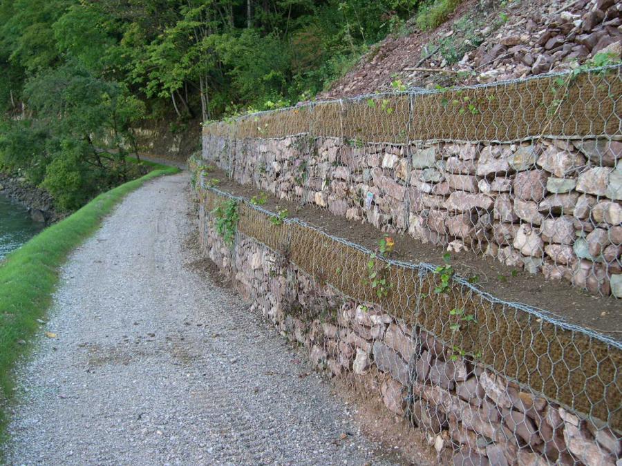 dei sassi dentro a delle reti metalliche gli uni sopra gli altri in una strada curva e degli alberi