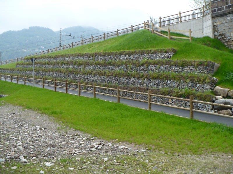 una strada con degli steccati in legno e dei sassi dietro a una rete metallica