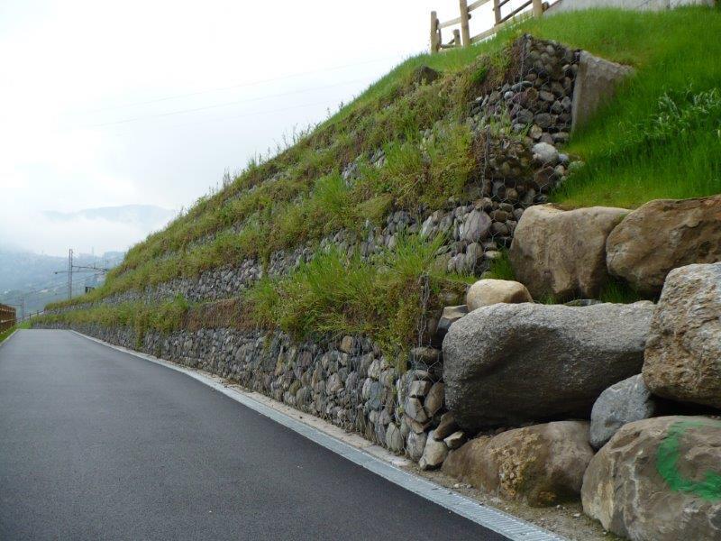 vista dei bordi di una strada con una rete metallica e dei sassi