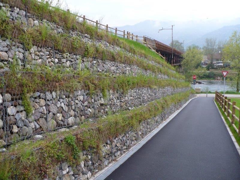 il bordo di una strada con una rete metallica e dietro dei sassi