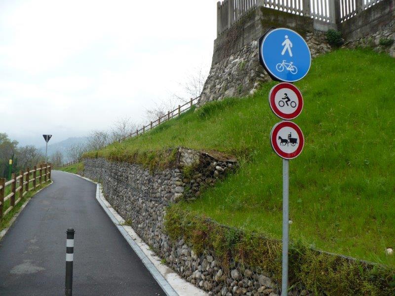 vista di una strada, sulla destra del prato e dei cartelli stradali