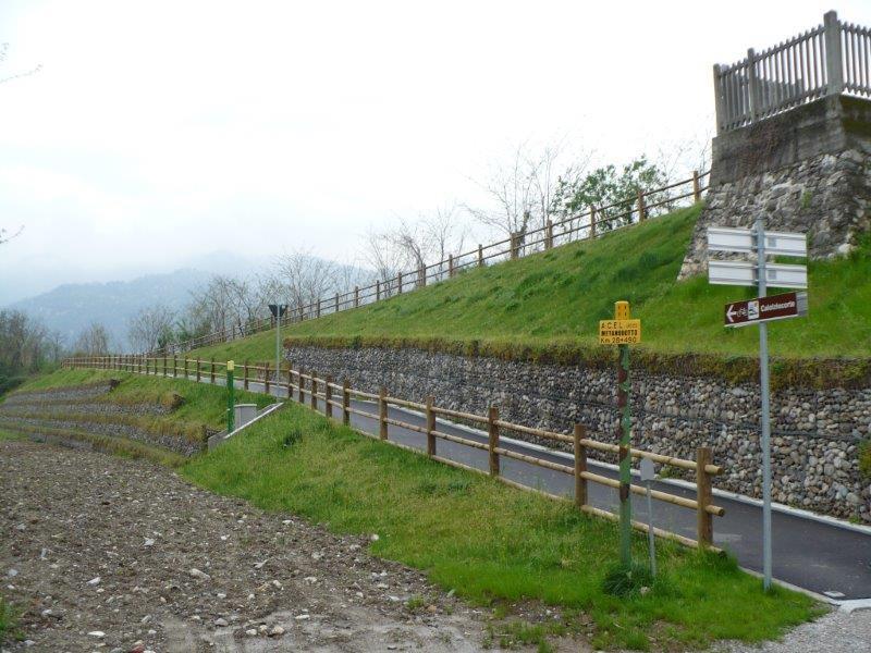 una strada di montagna con degli steccati in legno ai bordi