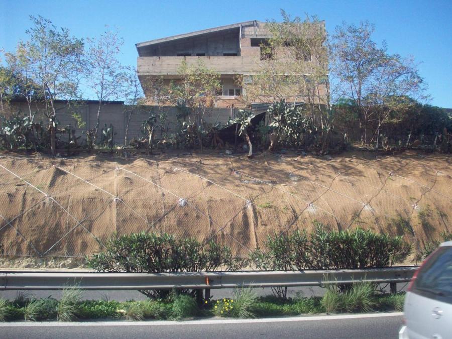 vista da lontano di una strada con i bordi ricoperti da una rete metallica e una casa