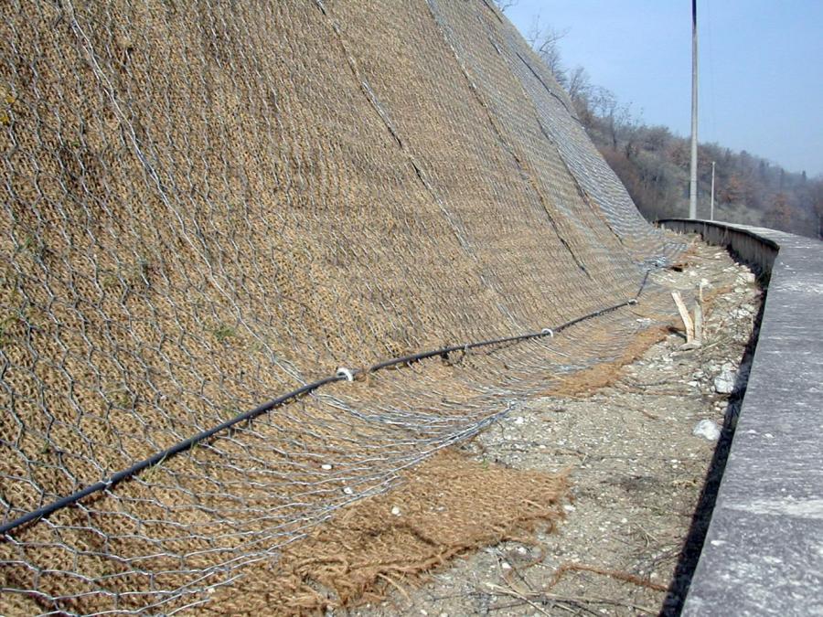 vista di una strada e una discesa di terra ricoperta da una rete metallica