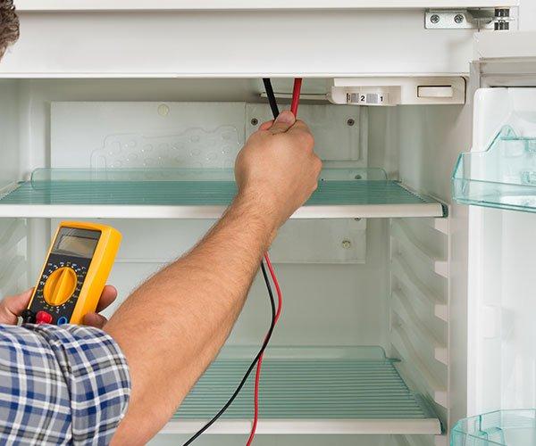 una mano con un tester che testa un frigorifero
