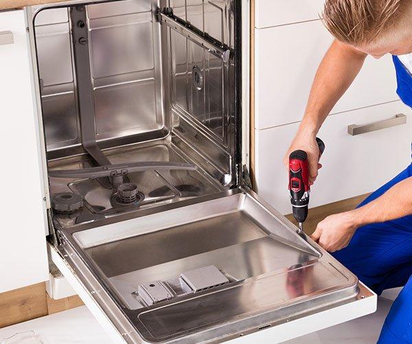 un tecnico con un trapano mentre avvita una vite di una lavastoviglie