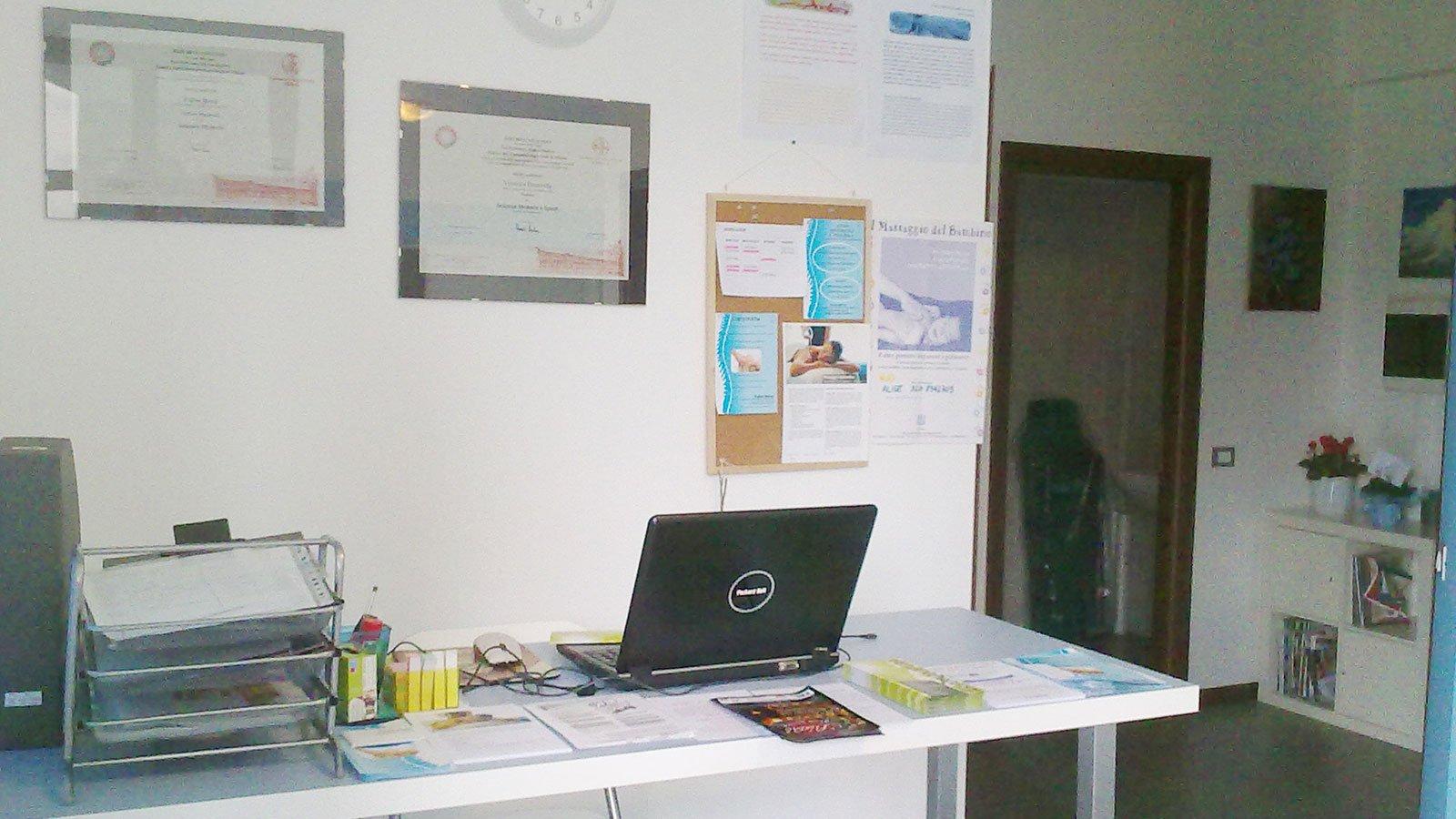 Una scrivania con un pc portatile e dei certificati appesi sul muro