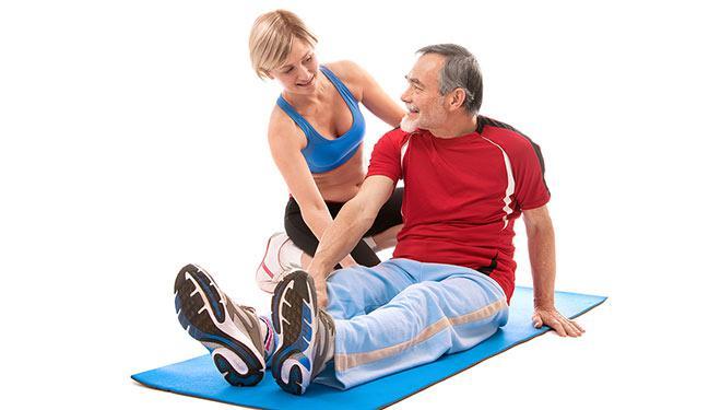 Un uomo seduto su un tappetino e una donna mentre spiega gli esercizi