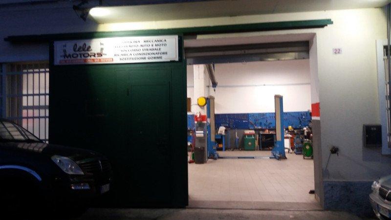 ingresso all'officina con una porta in ferro verde scorrevole con scritto Lele Motors