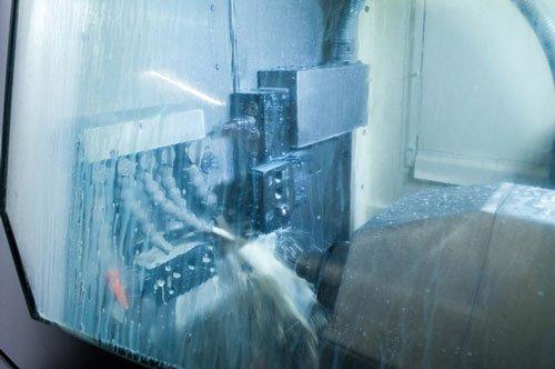 vista ravvicinata di un macchinario in metallo con una punta e dei tubi che spruzzano acqua