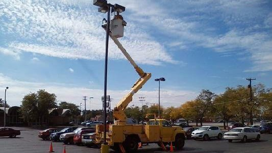 Dublin CPS, Inc. tech changing out light bulbs on a parking lot pole light.