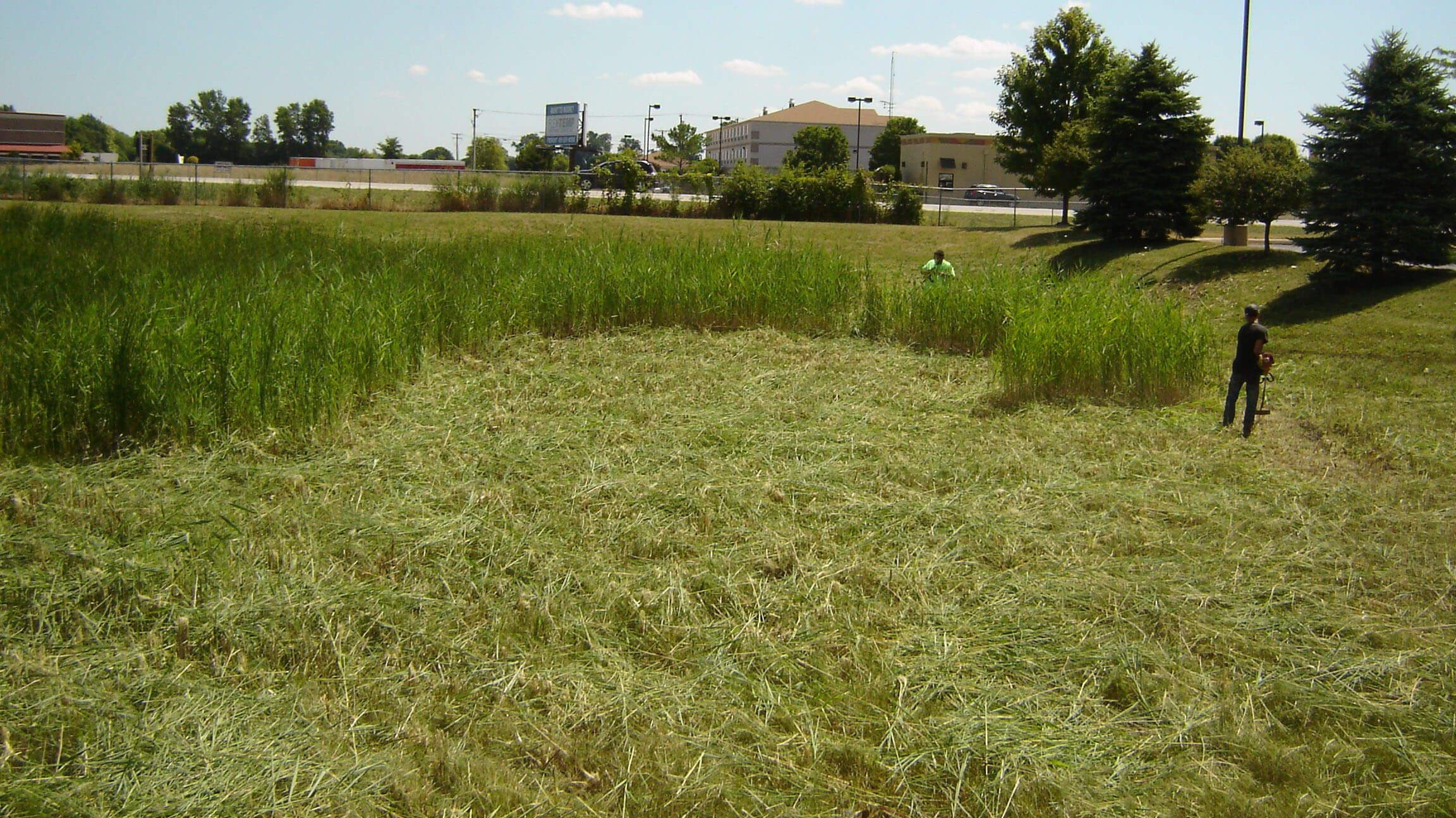 Dublin CPS, Inc. tech performing clean-up of rentention pond area at a commercial property