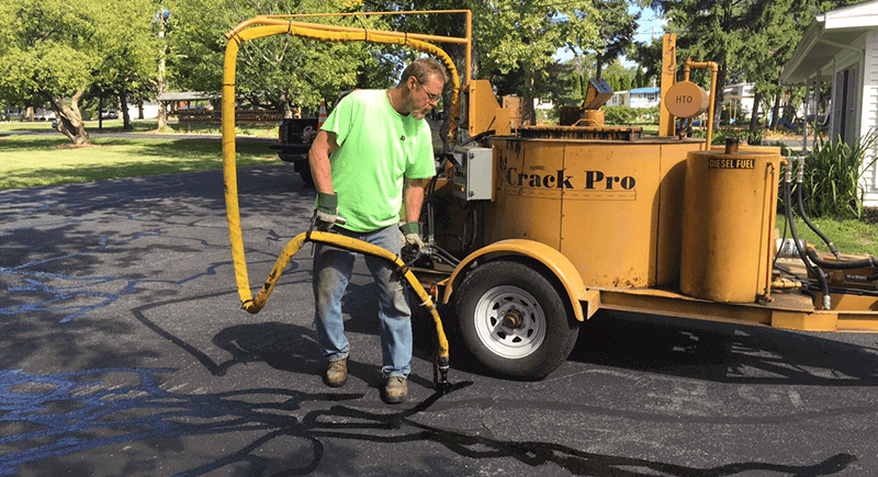 Dublin CPS, Inc. tech performing crack filling on a commercial parking lot