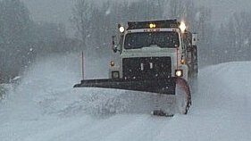 Plow truck removing snow from parking lot