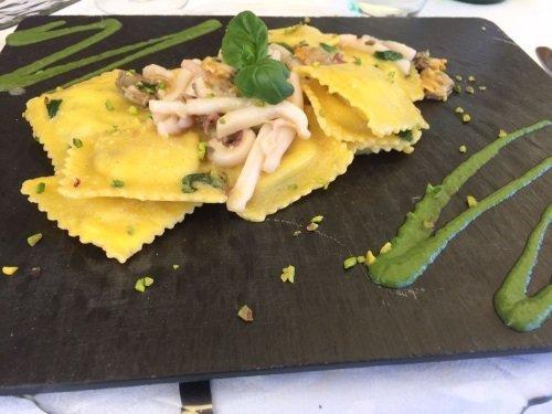 un piatto di ravioli con calamari e salsa verde