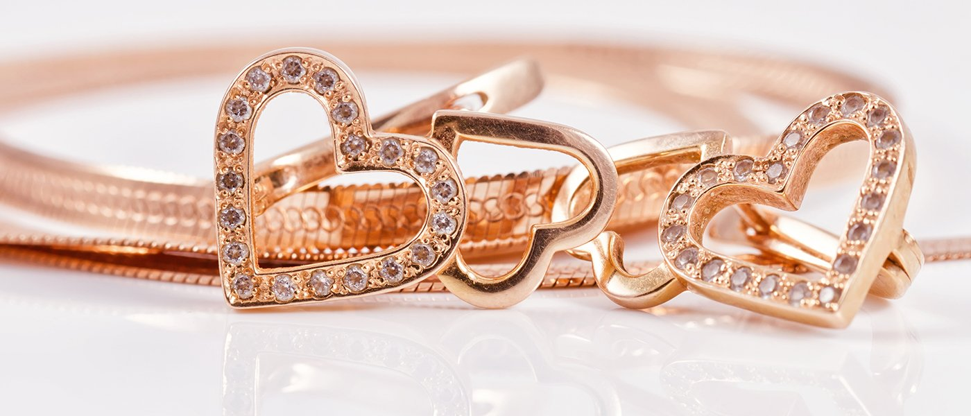 dei gioielli dorate a forma di cuoricini con dei diamanti
