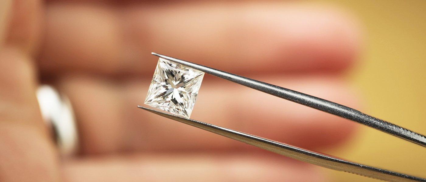 una pinzetta che tiene un diamante quadrato